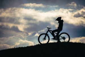silhouette of person riding on bicycle during daytime